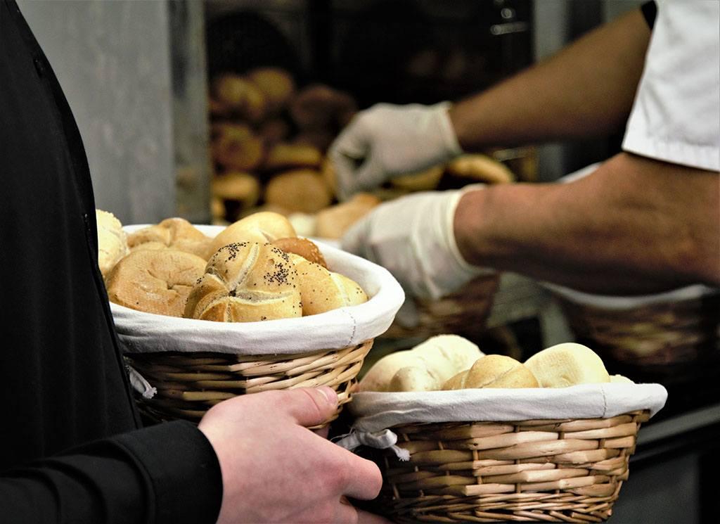 Un apprenti boulanger remplit un panier