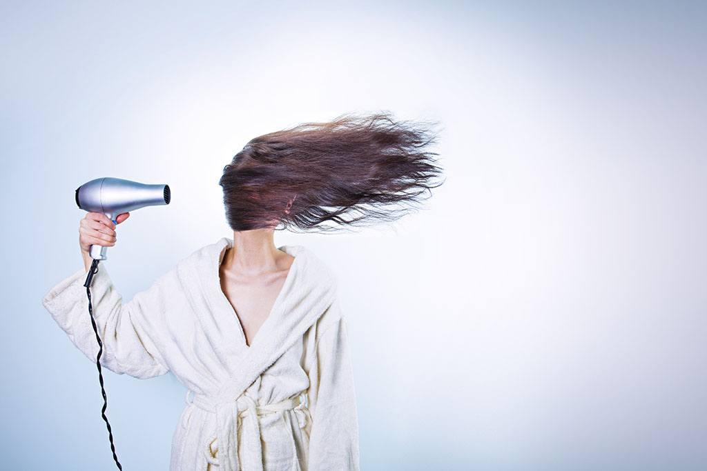 Une femme utilise un sèche cheveux